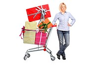A woman posing next to a shopping cart full with gifts isolated on white background