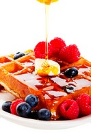 A stream of golden Canadian maple syrup adds the finishing touch to a delicious breakfast of belgian waffles with fresh raspberries and blueberries. S...