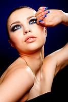 Close_up portrait of beautiful brunette with blue eye shadow make up and manicure