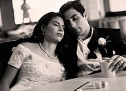 Bride and groom with eyes closed at diner