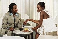 African couple holding hands at bar