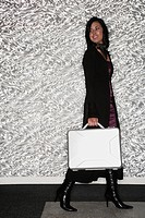 Hispanic businesswoman carrying briefcase