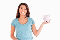 Attractive female holding a piggy bank while standing against a white background