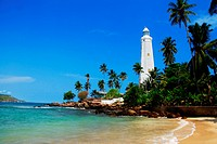 Beautiful white lighthouse Dondra Head, the southest cape of Sri Lanka _ seen from the beach. The lighthouse is also a highest 161 feet not only on th...