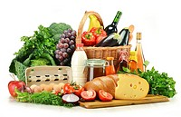 Groceries in wicker basket including vegetables, fruits, bakery and dairy products and wine isolated on white