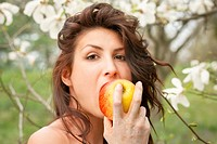 Beautiful young girl eating an apple in the park