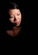 Soft contemplative look of beautiful asian woman on black background