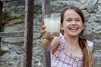 seven year old girl is drinking milk outside in the summer