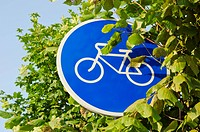 bicycle track blue sign and tree leafs
