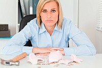 Sad woman sitting in her office in front of an shattered piggy bank with less in than expected