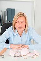 Sulking woman sitting in front of an shattered piggy bank looking into camera in her office