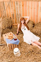 Red_hair young hippie woman breakfast on hay in barn country style