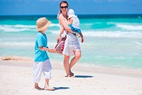 Mother and two kids walking along tropical beach