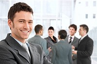 Smiling confident businessman portrait, group of businesspeople chatting in background.