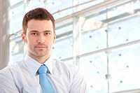 Portrait of handsome young businessman smiling front of window.