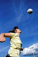 Real female soccer or football player during a match, reaching to hit the ball with her head and score a goal with sky and stadium spot lights in back...