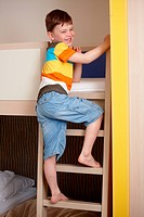 Smiling little boy going up the ladder of bunk bed.