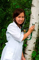 Young woman listens to a tree with a stethoscope