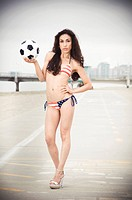 Beautiful model wearing the United States flag bikini on skates holding USA soccer ball at the beach sidewalk