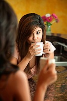Young Hispanic woman drinks coffee or tea with friend in kitchen