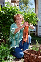 Senior woman holding fresh carrots and smiling