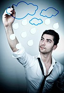 Young business man drawing rain clouds on a glass board