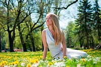 Smiling happy young terson teen girl sitting outdoors looking away