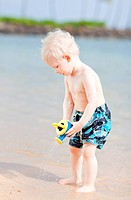 cute toddler using watering pot on a beach