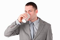 Businessman drinking coffee against a white background