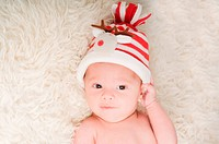 Newborn baby in chritstmas hat lies on fur