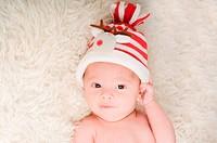 Newborn baby in chritstmas hat lies on fur