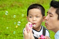 Asian father and son blowing bubbles outdoor