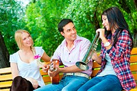 Young friends play the guitar and trumpet in the park