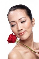 Close_up of a young Asian woman holding a flower