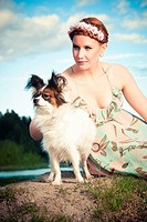 a redhaired beauy posing outdoor with a papillion dog also knows as continentinal toy spaniel