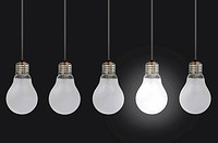 One lit bulb amongst a row of unlit bulbs, signifying uniqueness or innovative ideas
