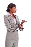Beautiful young ethnic african american business woman holding clipboard and writing using black pen. She is looking down at the paper with a serious ...