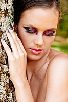 beautiful woman with dramatic eye makeup and long eyelashes wearing grey manicure standing by the tree looking down