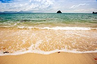 Tropical beach and coastline with waves lapping