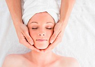 Closeup of a young pretty red_haired woman receiving a massage in a spa centre
