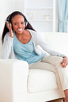 Smiling woman leaning against armrest while listening to music
