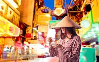 Young woman in traditional asian clothes eating rice noodles with chopsticks on an asian city street