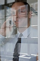 A businessman talking on a mobile phone, viewed through window