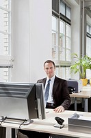 A businessman sitting at a desk in his office (thumbnail)