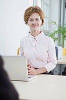 A businesswoman with a laptop sitting at her office desk