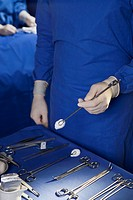 Midsection of a man holding a surgical instrument