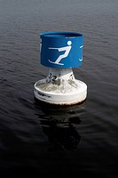A buoy with a symbol for waterskiing on a lake