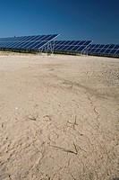 Dry ground next to rows of solar panels in a field