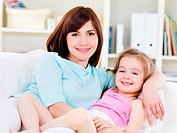 Portrait of happy young beautiful woman with little pretty daughter relaxing on a sofa at home