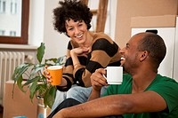 A laughing couple taking a coffee break while moving house, close-up (thumbnail)
